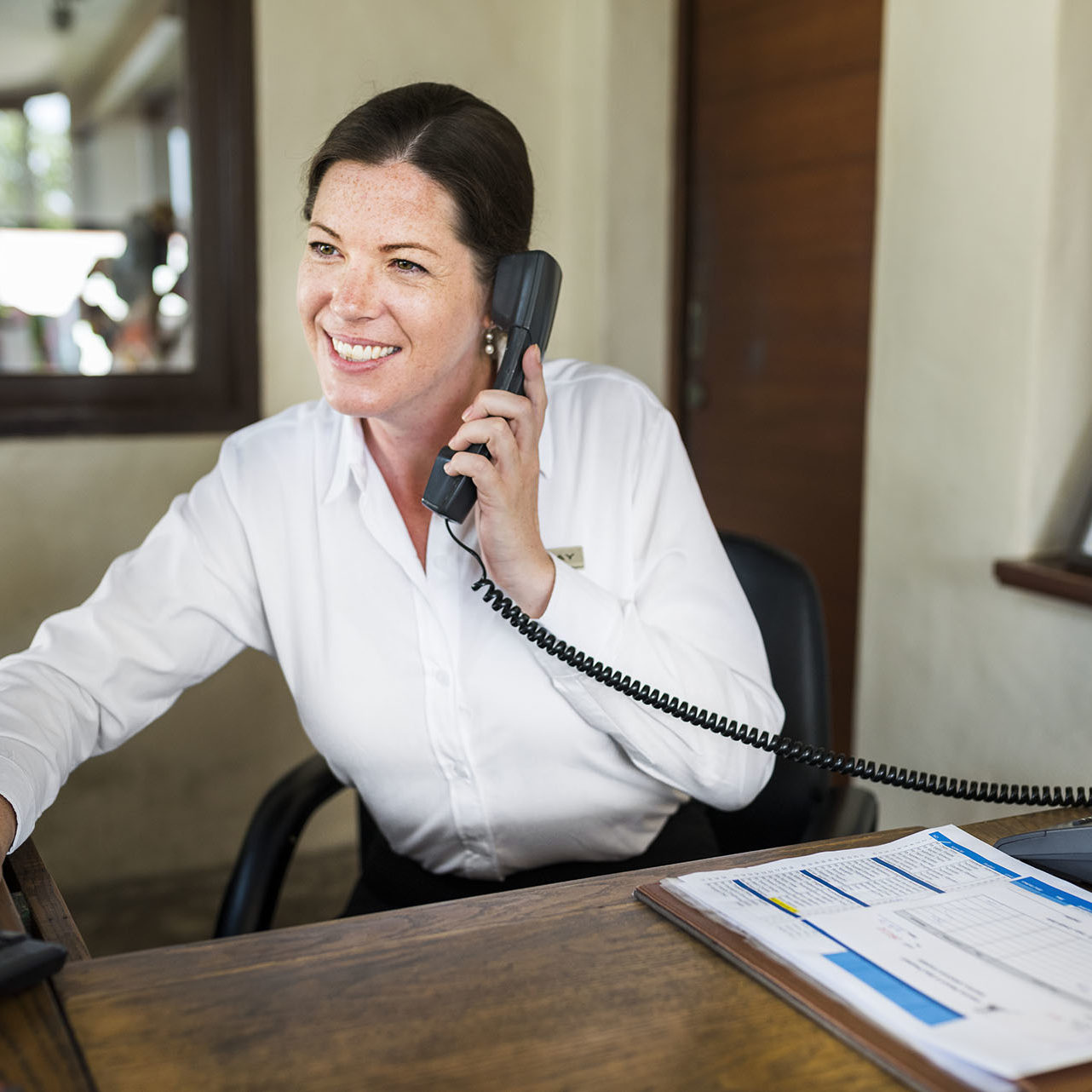 Female resort receptionist working at the front desk