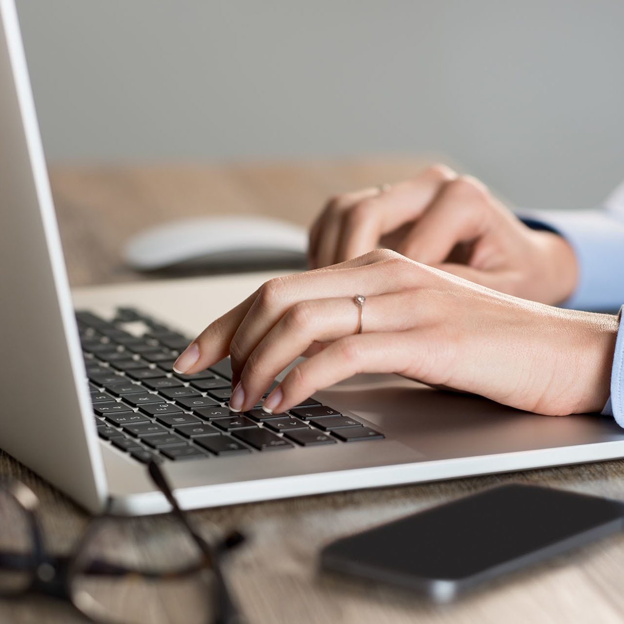 Closeup shot of a woman hand typing on keypad of her laptop. Secretary working in office at desk. Shallow depth of field with focus on typing on keypad of laptop.